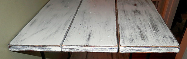 Close up photo of varnished wood shelves after being distressed and painted.