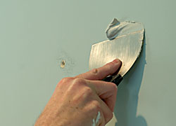 Applying first coat of drywall mud to repair a hole in the wall.