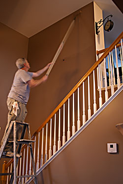 Two story room being painted and the use of a step ladder to reach the upper heights