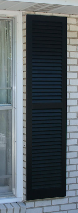 Louvered wooden shutter painted Tricorn Black.