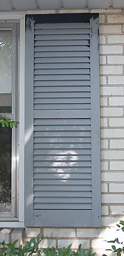 Louvered wooden shutter with primer applied.